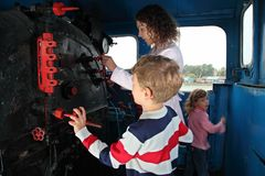 Mother with children in locomotive cabin Royalty Free Stock Photos