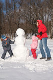 Mother and children make snowman Royalty Free Stock Photo