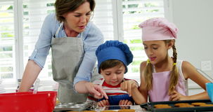 Mother and children making cookies in kitchen. Mother and children using digital tablet while making cookies in kitchen stock footage