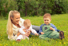 Mother with children on meadow stock photo