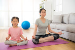 Mother with children meditating doing yoga. Young mother with cute female children meditating and doing yoga exercise at home in the living room on the Stock Images