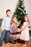 Mother and children near a fir-tree. Happy family with gifts near a new-year tree Stock Images