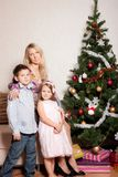 Mother and children near a fir-tree Stock Image