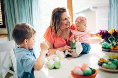 Mother and children painting colorful eggs. Mom, toddler and preschooler paint and decorate Easter egg Stock Photo