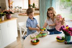Mother and children painting colorful eggs. Mom, toddler and preschooler paint and decorate Easter egg Stock Image