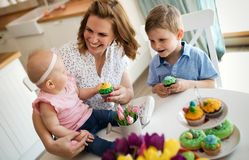 Mother and children painting colorful eggs. Mom, toddler and preschooler paint and decorate Easter egg Royalty Free Stock Photo