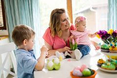 Mother and children painting colorful eggs. Mom, toddler and preschooler paint and decorate Easter egg Stock Photography