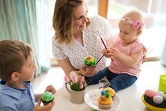 Mother and children painting colorful eggs. Mom, toddler and preschooler paint and decorate Easter egg Stock Images
