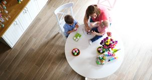 Mother and children painting colorful eggs. Mom, toddler and preschooler paint and decorate Easter egg Stock Photos