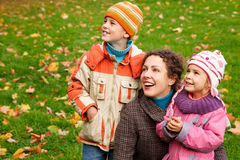 Mother with children in park. Mother with daughter and son looking up in autumnal park royalty free stock image