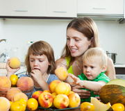 Mother and children with peaches Stock Photos