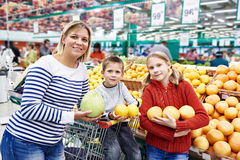 Mother and children with pineapples in fruit department in super Royalty Free Stock Photos