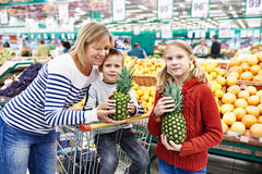 Mother and children with pineapples in fruit department of super Stock Photos