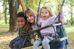 Mother with children playing. Mother with adopted children on the swing at the park Royalty Free Stock Image