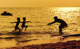 Mother and children playing on the beach Royalty Free Stock Images