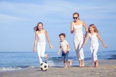 Mother and children playing on the beach at the day time. Stock Images