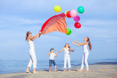 Mother and children playing on the beach at the day time. Stock Photos