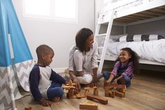 Mother And Children Playing With Building Blocks In Bedroom Royalty Free Stock Image