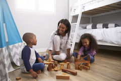 Mother And Children Playing With Building Blocks In Bedroom Royalty Free Stock Photos