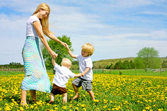 Mother and Children Playing and Dancing Outside in Flower Meadow. Mother and two children holding hands and dancing and playing outside in flower meadow stock photography