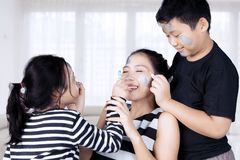 Mother and children playing with face painting Stock Photos