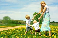 Mother and Children Playing Outside. A happy mother and two children; a young boy and his baby brother, are playing outside in a meadow of Dandelion flowers stock photography