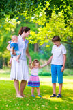 Mother and children playing in a park. Mother with children walking in the park on a very warm sunny summer day at sunset with beautiful clothes and adorable Stock Photos