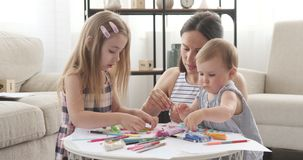 Mother and children playing with plasticine. Mother and little kids having fun playing with plasticine at home stock footage