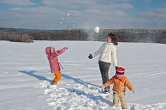 Mother and children playing with a snow Stock Images
