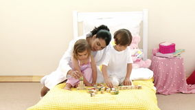 Mother and children playing with toy cubes on the bed Stock Photography