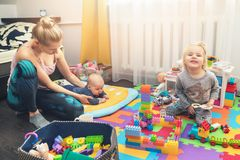 Mother and children playing with toys at home stock photography