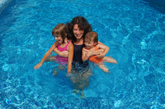 Mother and children in the pool Stock Photos