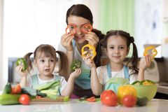 Mother and children preparing healthy food and having fun. Mother and her children daughters preparing healthy food and having fun Royalty Free Stock Photo