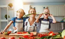 Mother with children preparing vegetable salad. At home stock images
