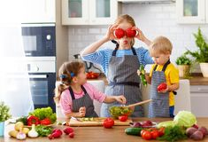 Mother with children preparing vegetable salad Stock Photos