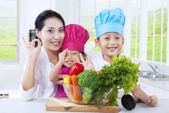 Mother and children preparing vegetables Stock Photography