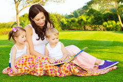 Mother with children read book. Photo of young mother with two cute kids reading book outdoors in spring time, happy mom teaching her children in the park, day Royalty Free Stock Photo