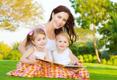Mother with children read book. Photo of attractive brunette women with two little smart children sitting down on green field in park in spring time and read Stock Image