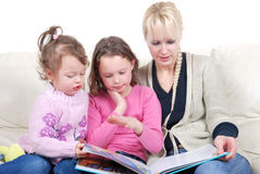Mother and children reading book stock photo