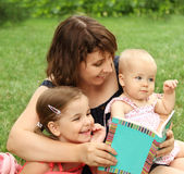 Mother and children reading a book i Stock Image