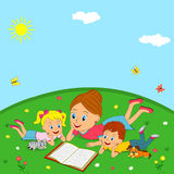 Mother and children are reading book on a meadow Stock Images
