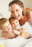 Mother With Children Relaxing In  Bath. Mother With Children Relaxing In Bubble Filled Bath Laughing Stock Images