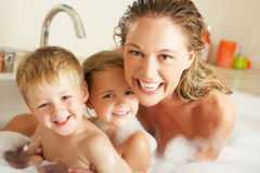 Mother With Children Relaxing In Bath. Mother With Children Relaxing In Bubble Filled Bath Stock Images
