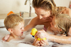 Mother With Children Relaxing In Bath. Mother With Children Relaxing In Bubble Filled Bath Smiling Stock Images