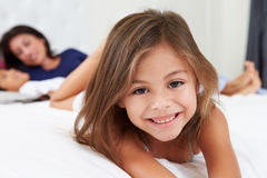 Mother And Children Relaxing In Bed Wearing Pajamas Stock Photography