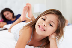 Mother And Children Relaxing In Bed Wearing Pajamas Stock Photo
