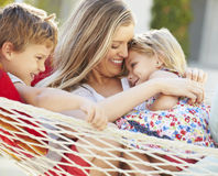 Mother And Children Relaxing In Garden Hammock Together Royalty Free Stock Image