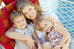 Mother And Children Relaxing In Garden Hammock Together Royalty Free Stock Photo