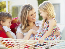 Mother And Children Relaxing In Garden Hammock Together Royalty Free Stock Photography