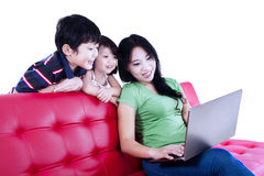 Mother and children relaxing on red sofa - isolated Royalty Free Stock Photos